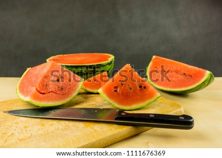 Cut portions of watermelon on a chopping board.