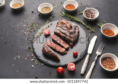 Cut rare rib eye steak with herbs and spices assortment on dark background, served with tomato and cutlery, restaurant serving, top view #1011897742