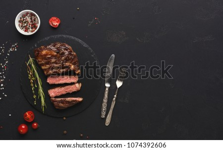 Cut rare rib eye steak with herbs and spices on dark background, served with tomato, restaurant serving with cutlery, top view, copy space