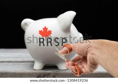 Cut savings RRSP concept with hand holding scissors towards a piggy bank