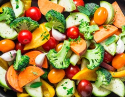 Cut seasonal raw vegetables - sweet potatoes, broccoli, bell peppers, zucchini, tomatoes, onions, garlic with spices and herbs. Ingredients to prepare vegetable side dish. Healthy vegetarian food