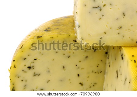 cut traditional Gouda cheese with herbs on a white background