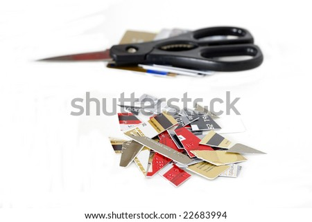 cut up credit cards with stack of cards and scissors in background