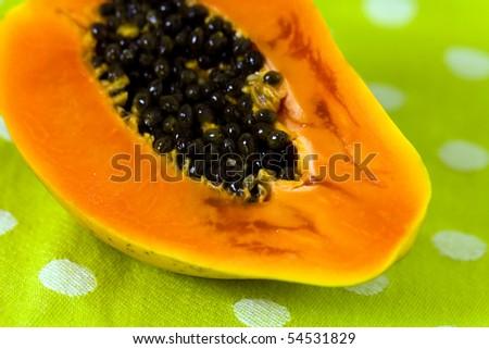 Cut up papaya fruit on green background