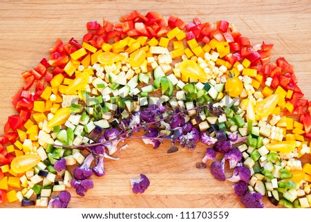 Cut vegetables arranged as a rainbow on wooden surface.Also available in vertical format.