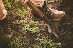 Cut view and close up of one man's foot in shoes on shovel and digging dark ground. Springtime with fresh green grass growing. Another feet stand on ground