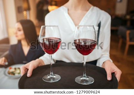 Cut view of waitress hold two glasses of red wine on tray. Youn businesswoman sit behind her at table and look left. She has salad bowl on table. #1279009624