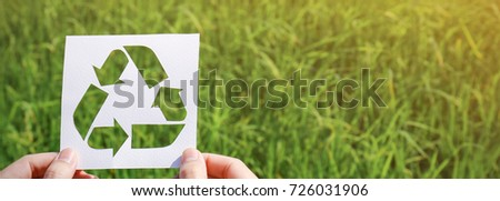 Cut white paper with the logo icon of recycling over green grass. Recycling sign and symbol world environment day background concept panoramic banner