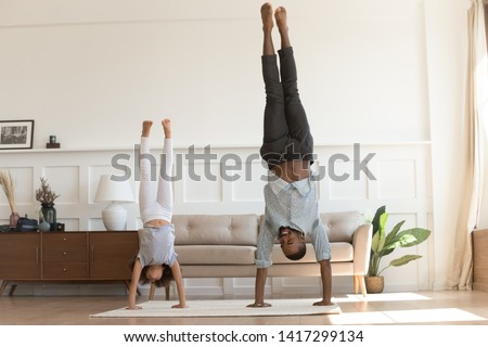 Cute active african kid girl copy imitate father doing gymnastic handstand exercise in living room, sporty family black dad and child daughter stand on hands upside down having fun together at home