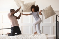 Cute active kid daughter playing pillow fight on bed with african american dad, happy mixed race father and funny little child girl having fun in bedroom black family enjoy leisure morning activity