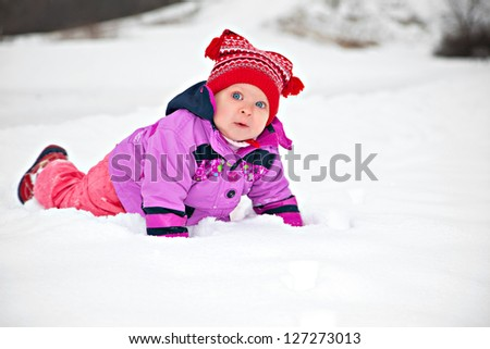 Cute adorable baby crawling in snow in winter park
