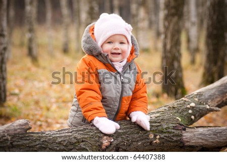 cute adorable baby smile and stay near fallen tree
