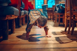 Cute adorable boy three years old having fun in cafe restaurant. Child playing on floor in public place. Freedom of self expression and behaviour for kids. Toddler touching dirty ground.