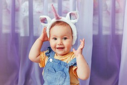 Cute adorable Caucasian baby girl wearing unicorn headband with horn and ears. Pretty funny child kid with head hair fairy tale animal accessory toy. Smiling toddler playing at home looking at camera.
