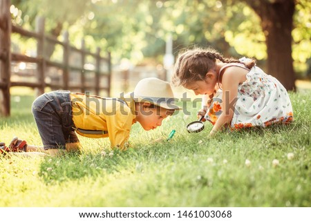 Cute adorable Caucasian girl and boy looking at plants grass in park through magnifying glass. Children friends siblings with loupe studying learning nature outside. Child education concept. Stock photo ©