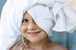 Cute adorable caucasian little blond girl wearing white towel on we head after shower or bathing at bathroom. Portrait of cheerful smiling female child