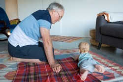 Cute adorable infant lying on belly and playing on soft floor at home. Serious grandfather sitting on rug near grandchild and watching little child. Nursery, family and infancy concept