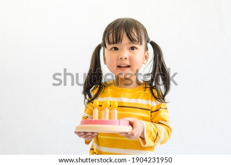 Cute adorable little asian toddler girl celebrating birthday while holding birthday cake wooden toy gift and blowing candles.Happy birthday party.isolated on white background at home.Happy Birthday.