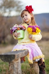 Cute adorable little girl holding bunch of flowers