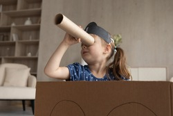 Cute adorable little girl in black pirate hat looking in spyglass, sitting in toy cardboard ship, preschool child kid wearing homemade costume holding cardboard tube as telescope, playing funny game