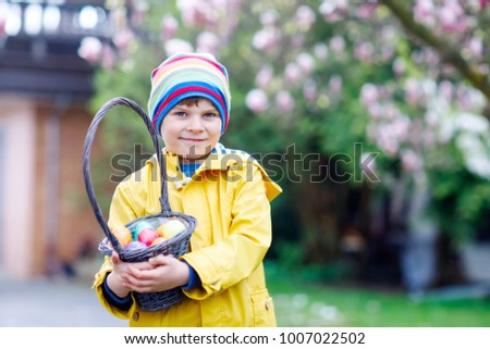 Cute adorable little kid boy making an egg hunt on Easter. Happy child searching and finding colorful eggs in domestic garden. Boy in spring clothes on cold day. Old christian and catholoc tradition