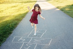 Cute adorable little young child girl playing hopscotch outdoor. Funny activity game for kids on playground outside. Summer backyard street sport for children. Happy childhood lifestyle.