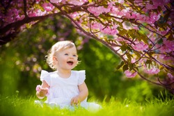 cute adorable nice baby girl in white spring dress smiling sitting under sakura tree