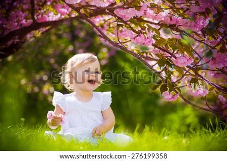 cute adorable nice baby girl in white spring dress smiling sitting under sakura tree