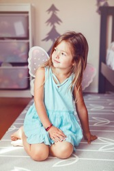 Cute adorable pretty dressed preschool girl playing fairy princess at home. Child creativity imagination and fantasy dreams concept. Beautiful Caucasian kid in blue dress pretending a fairy or elf.