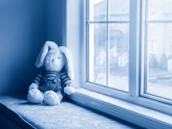 Cute adorable soft plush stuffed bunny animal sitting on windowsill. Child kids abandoned toy doll left alone. Toned with classic blue 2020 color.
