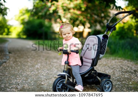 Cute adorable toddler girl sitting on pushing bicyle or tricycle. Little baby child going for a walk with parents on sunny day. - Shutterstock ID 1097847695