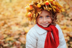 cute adorable toddler girl vertical portrait with bouquet of autumn leaves and wreath walking outdoor in park or forest, wearing warm knitted yellow snood