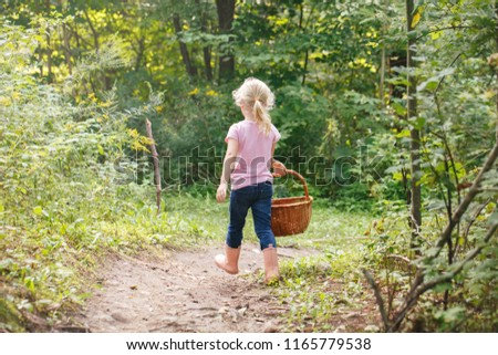 Cute adorable white Caucasian blonde preschool little girl picking fresh edible mushrooms in wicker basket. Autumn fall activity hobby concept.
