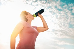 Cute adult woman in sportswear, drinking from a shaker. Blue sky and clouds in the background. Bottom view. Copy space. The concept of fitness and sports nutrition