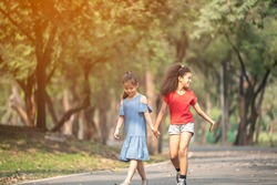 Cute african american and Asian little girl playing outdoor. Two little girl walking in the park.