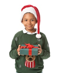 Cute African-American boy in Santa hat and with Christmas gift on white background