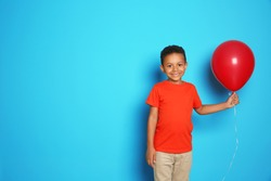 Cute African-American boy with balloon on color background. Birthday celebration
