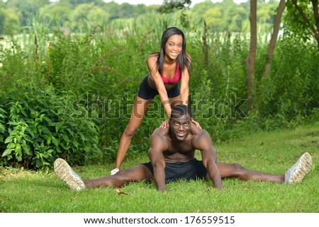 Cute African-American couple working out together in park - stretching before work out - woman in shorts and pink sports bra and male shirtless with shorts