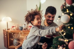 Cute african american girl decorating Christmas tree with dad.