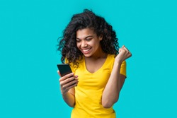 Cute african american girl in bright yellow t-shirt isolated on blue background smiling and showing winner gesture with her fist reading good news on her mobile phone. Young woman hit lottery  jackpot