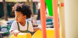 Cute African American little kid boy having fun while playing on the playground in the daytime in summer. Outdoor activity. Playing make believe concept. Outside education, Banner