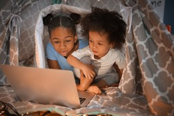 Cute African-American sisters with laptop watching cartoons in hovel