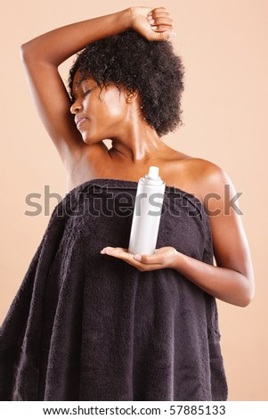 Cute African American using aerosol deodorant
