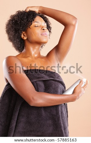 Cute African American using aerosol deodorant