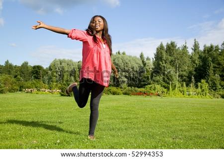 Cute African American woman having fun on grass