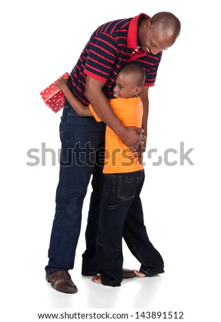 Cute african boy wearing a bright orange t-shirt and dark denim jeans is getting a gift from his father.