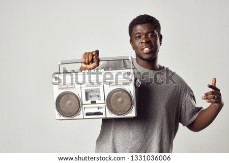 Cute African man holding in his hands a media player a gray background