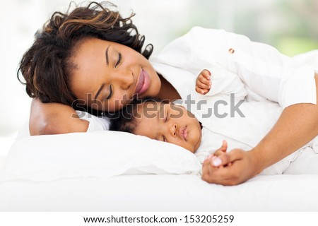 cute african mother and baby sleeping in bed