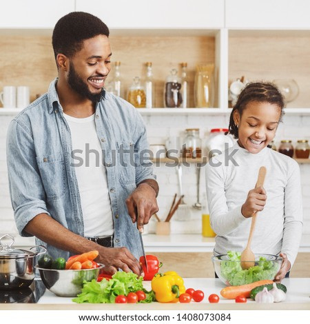 Cute afro kid girl and her father cooking fresh salad. Cooking vegetarian food together concept