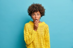 Cute amazed curly haired woman finds out shocking news stares at camera with wide opened mouth stands shocked and astonished wears casual yellow jumper isolated on blue background. Human reaction
